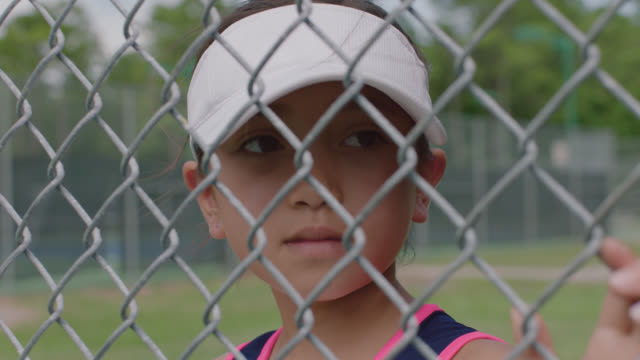 slow mo. cu. an athletic little girl watches her female role models playing tennis through a chainlink fence and looks into the camera - recinzione video stock e b–roll