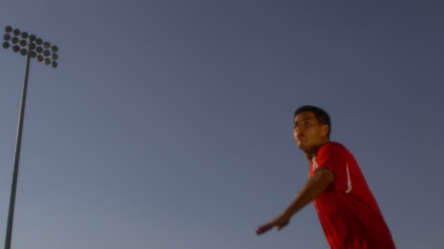 slo mo. an athletic soccer player kicks a ball over his head in a stadium - offense sporting position stock videos and b-roll footage
