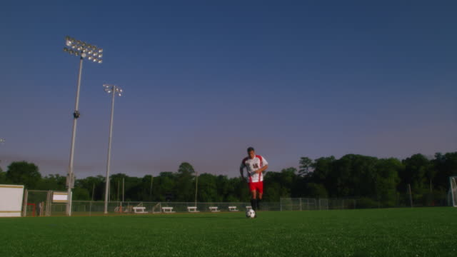 stockvideo's en b-roll-footage met slo mo. an athletic soccer player runs toward the camera kicking a soccer ball while running drills on an empty soccer field - dribbelen