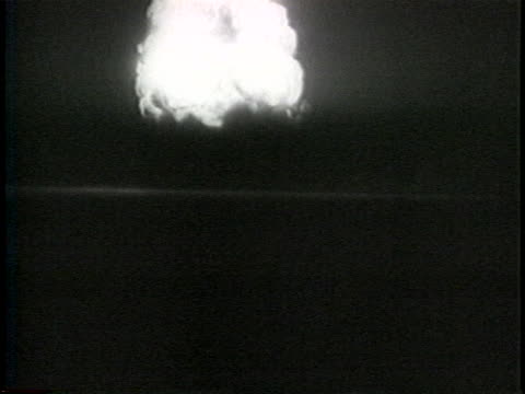 an atomic bomb explodes in the dark with a blinding explosion and resulting mushroom cloud. - atomic bomb stock videos & royalty-free footage