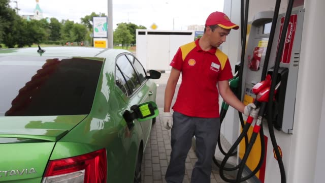an attendant refuels a customers automobile at a royal dutch shell plcs 150th gas station on its opening day in moscow russia on wednesday july 8... - gas station attendant stock videos and b-roll footage