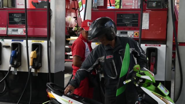 an attendant refuels motorcycles and receives payment at a pt pertamina gas station in jakarta indonesia on wednesday jan 21 2015 - gas station attendant stock videos and b-roll footage
