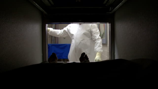 vidéos et rushes de an attendant removes a cadaver from a morgue compartment. - autopsie