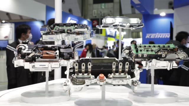 An attendant second from left speaks to a visitor in front of a display of Keihin Corp's EDrive system at the Automotive World 2018 forum in Tokyo...