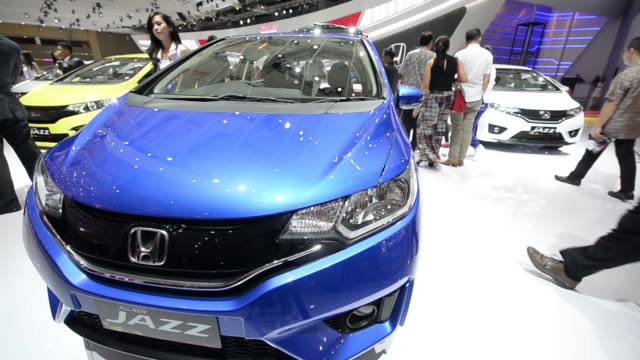 an attendee checks the instrument panel inside a car on display a model stands next to a honda jazz car medium view and pan of a honda jazz car wide... - trade show booth stock videos & royalty-free footage