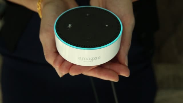 An attendee holds and asks questions of an Echo Dot device during the UK launch event for the Amazoncom Inc Echo voice controlled home assistant...