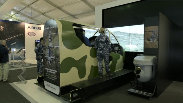 an attendee operates a lockheed martin co. target sight system , while seated in a textron inc. bell helicopter ah-1z viper simulator, in the... - plc stock videos & royalty-free footage