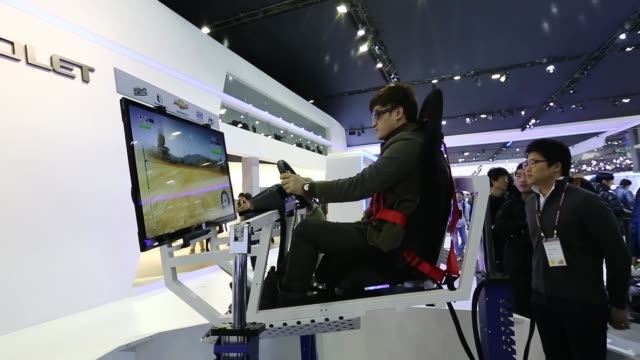 an attendee plays a motor racing game at the gm korea co chevrolet booth during the press day of the seoul motor show in goyang the seoul motor show... - goyang stock videos and b-roll footage