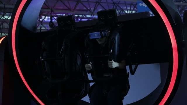 vídeos de stock, filmes e b-roll de an attendee tries out sangwha's gyro vr attraction at the tokyo game show 2017 at makuhari messe in chiba, japan, on friday, sept. 22, 2017 - game show