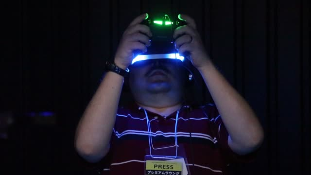 vidéos et rushes de an attendee tries out the sony computer entertainment inc project morpheus virtual reality headset at the tokyo game show 2014 in chiba japan a booth... - casque téléphonique