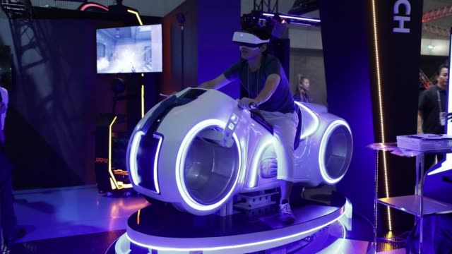 stockvideo's en b-roll-footage met an attendee wears a virtual reality headset while trying out jppvr co.'s photon bike in the company's booth at the tokyo game show 2017 at makuhari... - television game show