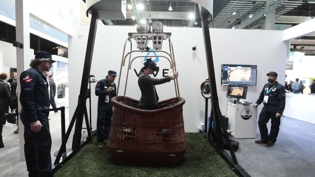an attendee wears a vive virtual reality headset and vive virtual reality sensors manufactured by htc corp to experience a virtual hot air balloon... - exhibition stock videos and b-roll footage