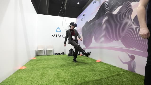 an attendee wears a vive virtual reality headset and vive virtual reality sensors manufactured by htc corp to play virtual soccer on the htc corp... - exhibition stock videos and b-roll footage