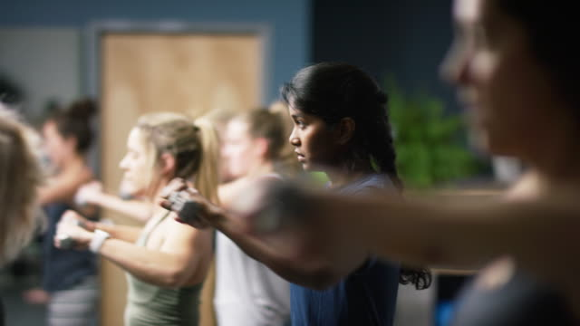 an attractive asian indian woman in her twenties performs shoulder exercises with hand weights with other women at a barre exercise studio - pilates stock videos and b-roll footage