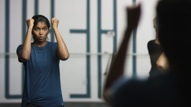 an attractive asian indian woman in her twenties with arms outstretched performs shoulder exercises with a group of women in a front of a mirror at a barre exercise studio - barre stock videos & royalty-free footage