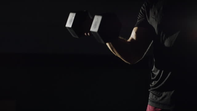 an attractive bearded caucasian man in his twenties performs bicep curls with a dumbbell in a dramatically lit gym (tight shot) - bicep stock videos & royalty-free footage