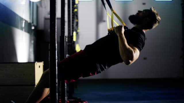 an attractive caucasian man in his twenties with a beard performs pull-ups with straps in a dramatically lit gym (wide shot) - pull ups stock videos & royalty-free footage
