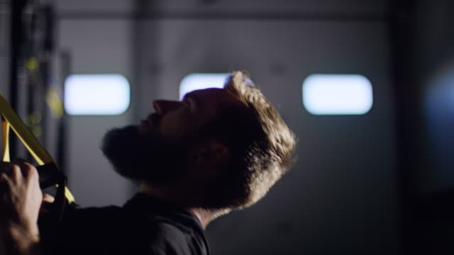 an attractive caucasian man in his twenties with a beard performs pull-ups with straps in a dramatically lit gym (tight shot) - chin ups stock videos and b-roll footage