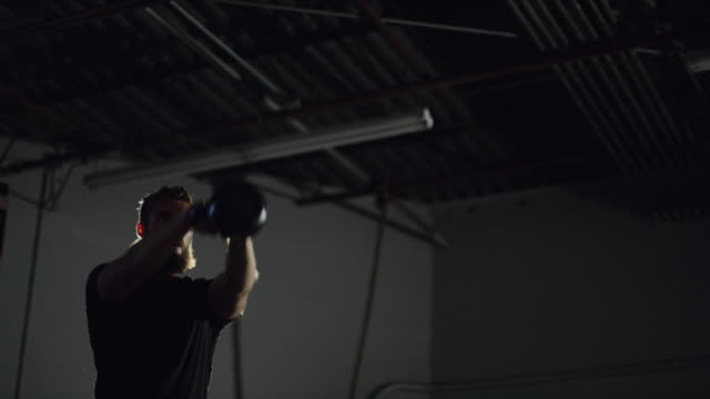 an attractive caucasian man in his twenties with a beard performs kettlebell swings in a dramatically lit gym (wide shot) - kettlebell stock videos & royalty-free footage