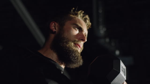 An Attractive Caucasian Man in His Twenties with a Beard Performs Bicep Curls with a Dumbbell in a Dramatically Lit Gym (tight shot)