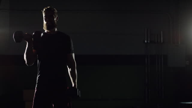 an attractive caucasian man in his twenties with a beard performs bicep curls with a dumbbell in a dramatically lit gym (medium shot) - raggomitolato video stock e b–roll