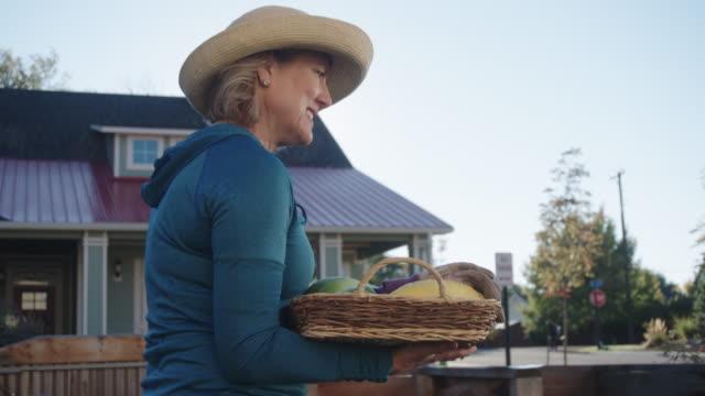 stockvideo's en b-roll-footage met een aantrekkelijke kaukasische vrouw in haar jaren vijftig loopt door haar moestuin zoals ze een mand draagt vol groenten in een buurt - alleen oudere vrouwen