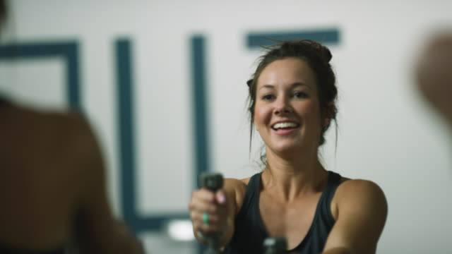 an attractive caucasian woman in her twenties performs shoulder exercises with hand weights in a class at an exercise studio - health club stock videos & royalty-free footage