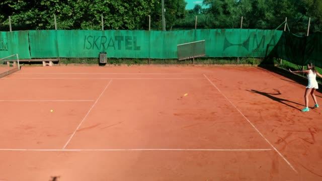 vidéos et rushes de une séduisante femmes mûres, jouer au tennis dans une tenue sportive blanche - terrain de sport sur gazon