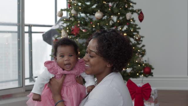 vídeos de stock, filmes e b-roll de uma mãe atraente brinca carinhosamente com sua filha bebê no dia de natal - tradição