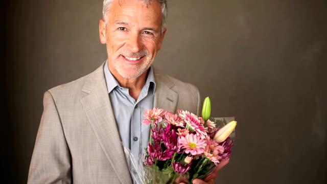 Un atractivo hombre senior sonriendo en una suite y sosteniendo un ramo de flores frescas