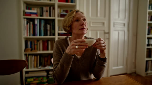 an attractive senior woman is enjoying a cup of hot tea - en dag i livet bildbanksvideor och videomaterial från bakom kulisserna