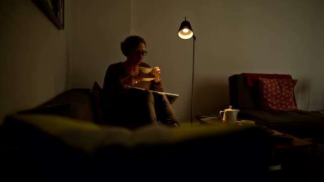 stockvideo's en b-roll-footage met an attractive senior woman is lying comfortably on her couch and enjoying a cup of hot tea - elektrische lamp