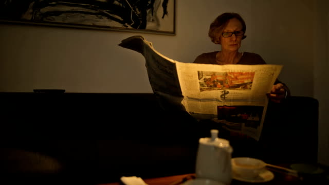 vídeos de stock, filmes e b-roll de an attractive senior woman is lying comfortably on her couch and reading a newspaper - óculos de leitura