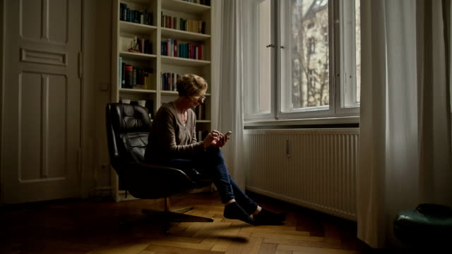 an attractive senior woman is sitting comfortably in a chair and typing on her smartphone - vidbild bildbanksvideor och videomaterial från bakom kulisserna