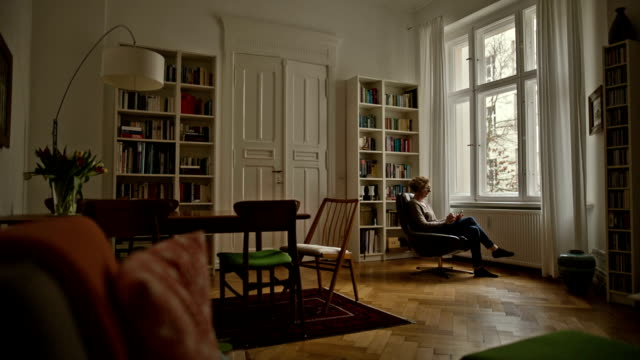 an attractive senior woman is sitting comfortably in a chair and typing on her smartphone - en dag i livet bildbanksvideor och videomaterial från bakom kulisserna
