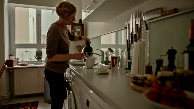 vídeos de stock e filmes b-roll de an attractive senior woman pours hot water into a teapot - um dia na vida de
