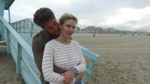 An attractive young couple embracing on the beach at sunrise. Santa Monica, California, USA.