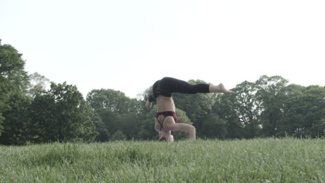 An attractive, young woman performs Yoga, alone in nature - 4k - slow motion