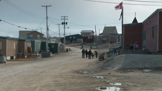 vídeos de stock e filmes b-roll de an atv and a motorbike ride up a dirt road in the inuit town of igloolik in canada - inuit