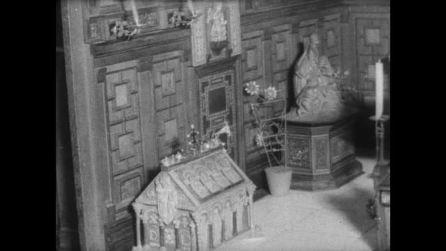 CU an auction catalog with 'Titania's Palace' written on the front / woman removes glass side of ornate vintage doll's house / CU doll's house chapel...