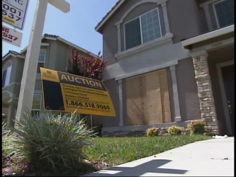 an auction sign stands on the lawn of a boarded up foreclosed home. - 2008 stock videos & royalty-free footage