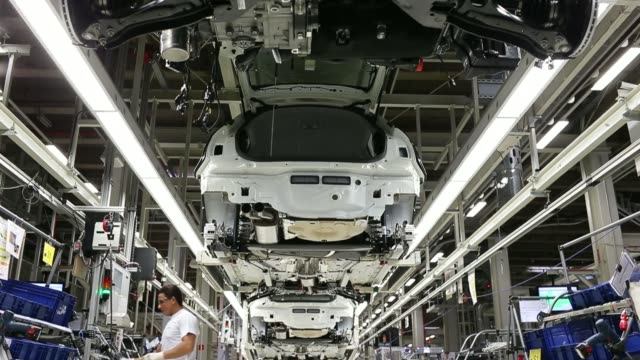 An Audi A1 automobile moves along a raised section of the production line at the Audi AG factory in Vorst Belgium on Tuesday June 17 Employees work...