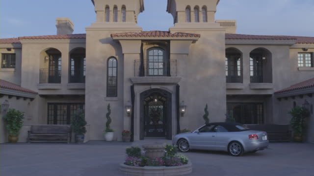 An Audi convertible moves away from a mansion.