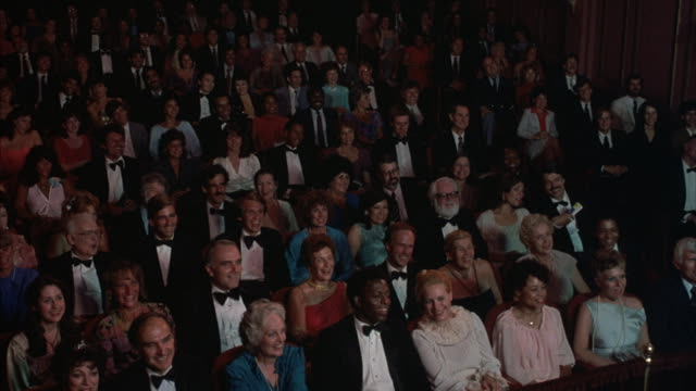 An audience gives a standing ovation in a theater.