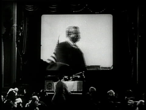 an audience in a theater watches a newsreel of president theodore roosevelt as a woman plays the piano - 無声映画点の映像素材/bロール
