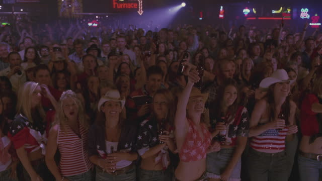 an audience in cowboy hats cheering and dancing at a concert. - country and western stock videos & royalty-free footage