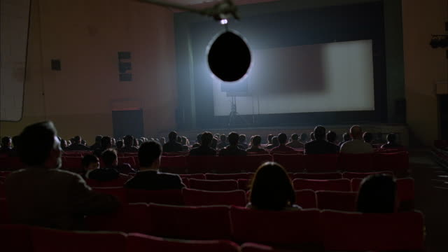 an audience sits in a movie theater. - projection screen stock videos & royalty-free footage