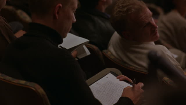 An audience takes notes in a lecture hall.