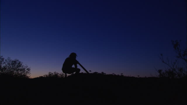 an australian aboriginal man squats on a rock and plays a didgeridoo at twilight. - aboriginal australian ethnicity stock videos & royalty-free footage