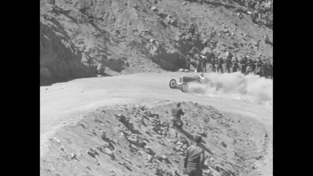 an auto speeds past the white flag with a lot of exhaust and dust / people in warm clothes watch the race far far below one rounds a hairpin turn and... - hair accessory stock videos & royalty-free footage